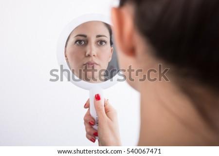 woman looking herself mirror の写真素材 今すぐ編集 540067471