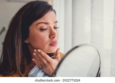 Woman looking herself in the mirror at home standing by the big window. She is concerned about acne, maskne