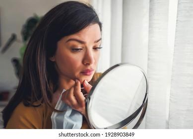 Die Frau sieht sich im Spiegel zu Hause an dem großen Fenster an. Sie macht sich Sorgen um Akne, Maskne