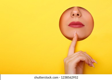 Woman looking in the hole, bright beautiful makeup, big eyes and lips, bright lipstick, professional cosmetics and facial care. Bright colored background and a gap slot in the paper.