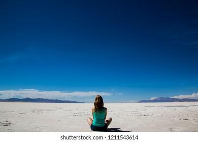 Woman looking at the horizon in the salt flats of Salinas Grandes, Jujuy / Salta
