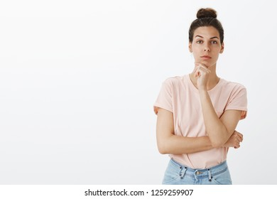 Woman looking with interest at camera as coworker telling good idea might work. Good-looking european female holding hand on chin raising one eyebrow and staring focused thinking listening team plan