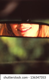 woman looking into car mirror