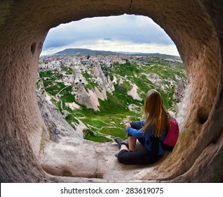 Woman looking into the distance against the background of incredible landscape with  mountains , geological structures in Goreme, Cappadocia,  Turkey