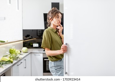 Woman looking into the fridge while cooking healthy food on the modern kitchen at home
