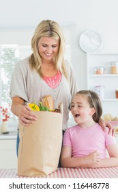 Woman looking into grocery bag beside smiling daughter in the kitchen