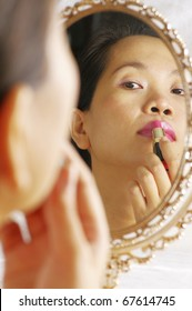 woman looking into mirror for applying lipstick on lips