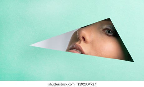 A woman looking into the opening of the triangle, a bright beautiful make-up, big eyes and lips, lipstick, professional cosmetics and facials. Bright color background and crevice in paper