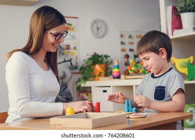 Woman looking at kid playing with didactic colorful toys indoors - preschool