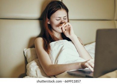 Woman looking at laptop on bed