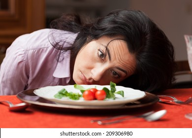 Woman looking to a little salad is tired about diet.