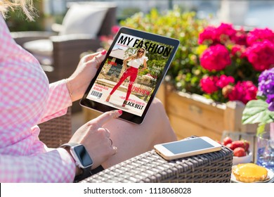 Woman looking at magazine cover on digital tablet