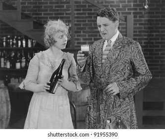 Woman looking at man making faces while tasting alcoholic beverage