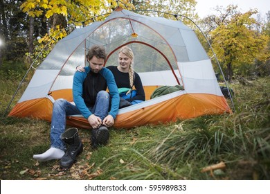 Woman Looking At Man Wearing Hiking Boot In Tent