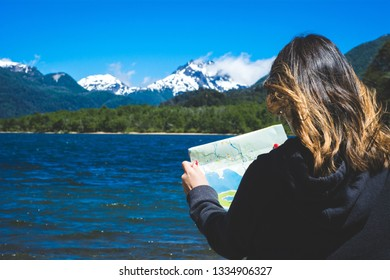 Woman looking at a map with mountains in the background. Travel concept.