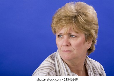 woman looking melancholy on blue back ground
