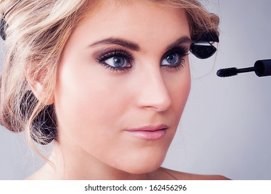 Woman looking in a mirror and applying eye makeup.