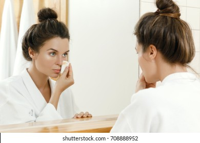Woman is looking in to the mirror and removing makeup with a cotton pad