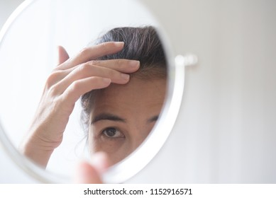 woman is looking at the mirror to see her hair loss problem. gray hair problem for middle ages woman