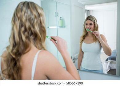 Woman looking in mirror while brushing her teeth in bathroom at home