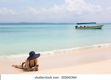 Woman looking at mobile phone on the beach