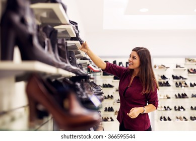 Woman is looking for a new pair of shoes. Shallow depth of field.