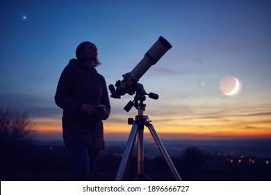 Woman looking at night sky with amateur astronomical telescope.