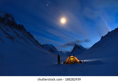 Woman looking at the night sky while camping in the snow covered mountains in Swedish Lapland (Nallo).