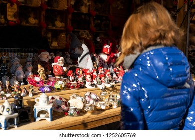Woman looking on handmade christmas decorations made out of porcelain on the christmas market of meran in south tyrol, Italy an thinks about buying some of them