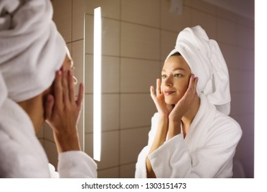 Woman looking on her mirror in bathroom