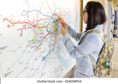 A woman looking on Japanese underground Japan Railway Map, Looking for her Train in Tokyo station. Tourism lost in Japan. Travel to Japan, Self Travel using public transportation