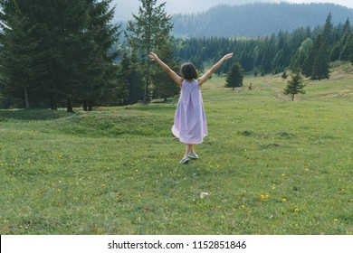 woman looking on mountains and holding hands up