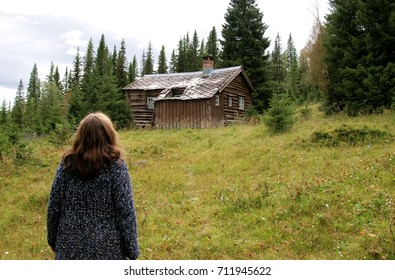 Woman looking up on an old cottage
