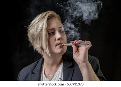 Woman looking on the side while smoking electronic cigarette