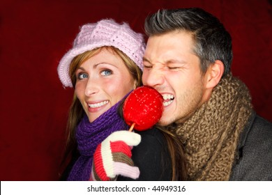 Woman looking on tasty red candy toffee taffy apple on christmas holiday market fair which is eaten by male boyfriend