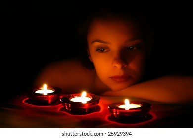 Woman looking on three red candles