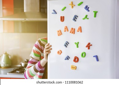 Woman looking in open fridge with Mama letters on door. Cooking for family and children concept