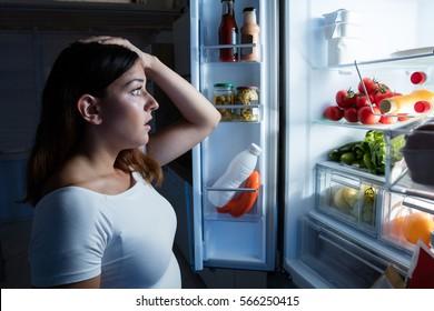 Woman Looking In Opened Fridge