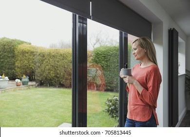 Woman is looking out of her patio door windows with a cup of tea in her hands.