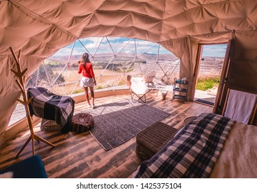 Woman looking out at nature from geo dome tents. Green, blue, orange background. Cozy, camping, glamping, holiday, vacation lifestyle concept. Outdoors cabin with scenic background. New Zealand.