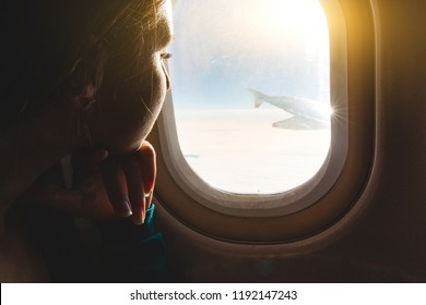 Woman looking out through airplane window from an over wing seat. Travel concept, also solitude and loneliness.