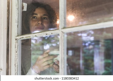 Woman looking out through an old window and holding a cup of coffee or tea. Beautiful and thoughtful girl with curly hair standing behind the window in a wooden cottage