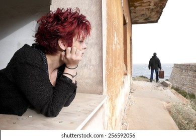 Woman looking out of the window at a man leaving her house