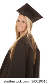 A woman looking over her shoulder in her cap and gown with a smile on her face.