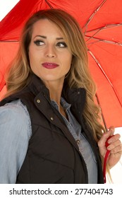 A woman looking over her shoulder holding on to her umbrella.
