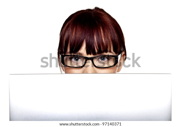 A woman looking over the top of a laptop computer at you. Looking at technology.