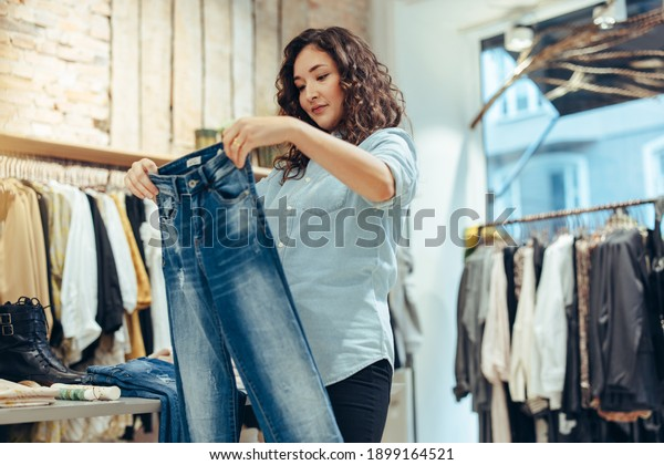 Woman looking at pair of jeans in a fashion store. Female customer buying jeans in clothing store.