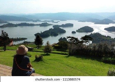 A woman looking at a panoramic view of Lake Bunyonyi (Place of many little birds) from Arcadia cottages  in south-western Uganda between Kisoro and Kabale, east Africa