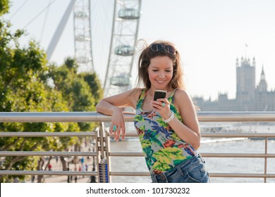 Woman looking at phone smiling, texting from bridge over River Thames, London with attractions in background