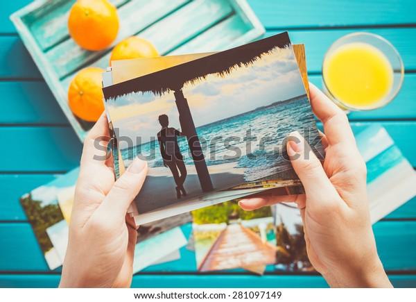 Mujer mirando fotos en sus manos. Vista superior.